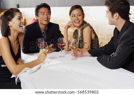 Couples sitting in restaurant, drinking wine and talking