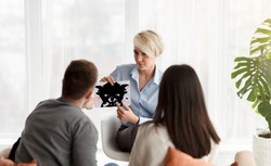 Couples Therapy Session. Marital Therapist Showing Spouses Inkblot Picture Testing Them Sitting In Office. Selective Focus