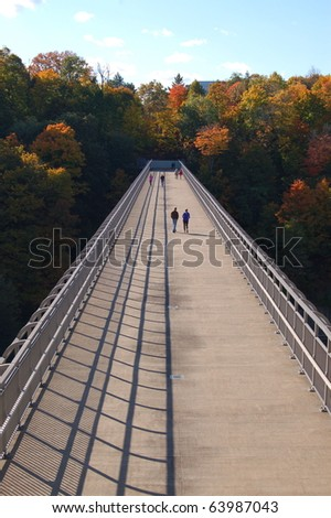 Couples walk on footbridge over river and enjoy autumn colors/Autumn Footbridge/Scenic Walk on Sunny Autumn Afternoon.