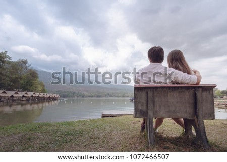 Couples who are hugging on the beach bench happily in the evening on the beautiful backdrop of the beautiful lake and the backdrop of the sky filled with dark, dark clouds. Love Friendship Concept
