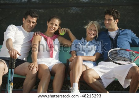 Couples with Tennis Rackets and Balls