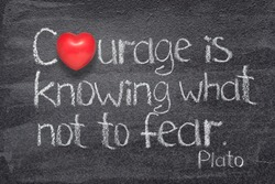 Courage is knowing what not to fear quote of ancient Greek philosopher Plato written on chalkboard with red heart symbol instead of O