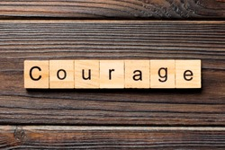 Courage word written on wood block. Courage text on wooden table for your desing, concept.
