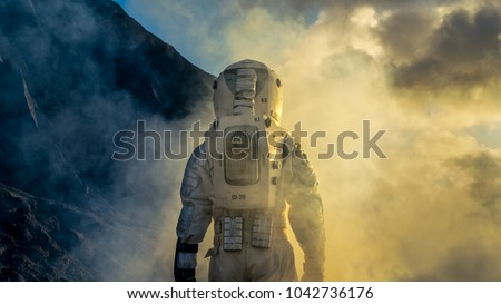 Courageous Astronaut in the Space Suit Explores Mysterious Alien Planet Covered in Mist. Adventure. Space Travel, Habitable World and Colonization Concept. #1042736176