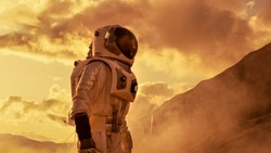Courageous Astronaut in the Space Suit Explores Red Planet Mars Covered in Mist. Adventure. Space Travel, Habitable World and Colonization Concept.
