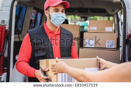 Courier delivering packages with truck while wearing protective face mask for coronavirus prevention - Focus on man worker Stockfoto ©