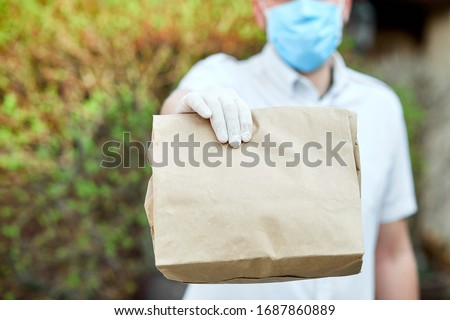 Courier, delivery man in medical latex gloves safely delivers online purchases in brown paper bags to the door during the coronavirus epidemic, COVID-19. Stay home, safe concept.