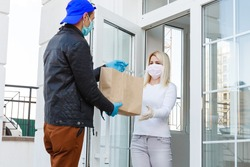 Courier, delivery man in protective mask and medical gloves delivers takeaway food. Delivery service under quarantine, disease outbreak, coronavirus covid-19 pandemic conditions. Stay home
