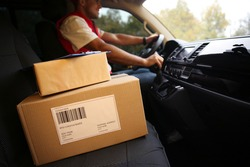 Courier driving delivery van, focus on parcels and clipboard