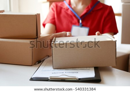 Courier hands giving packaged parcel at table #540331384