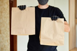 Courier in black hold go box food, delivery service, Takeaway restaurants food delivery to home door. Stay at home safe lives from coronavirus outbreak. Contactless delivery service under quarantine.