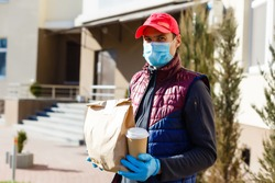 Courier in protective mask and medical gloves delivers takeaway food. Delivery service under quarantine, disease outbreak, coronavirus covid-19 pandemic conditions.