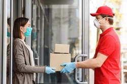 Courier in protective mask delivers packages to door. Girl picks up boxes