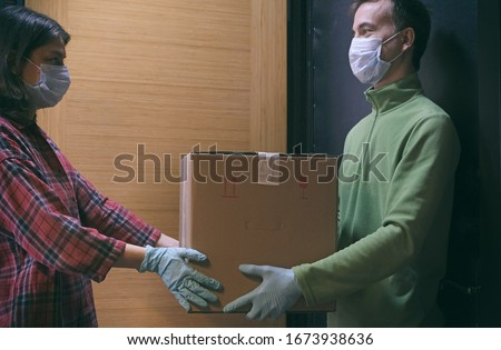 Courier in protective mask delivers parcel, customer in medical gloves receives box. Delivery service under quarantine, disease outbreak, coronavirus covid-19 pandemic conditions.