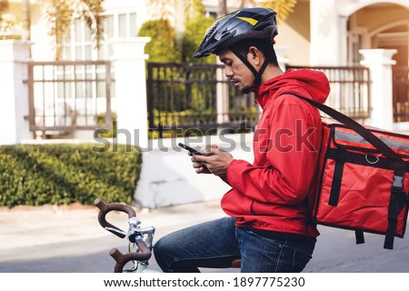 Courier in red uniform with a delivery box on back riding a bicycle and looking on the cellphone to check the address to deliver food to the customer. Courier on a bicycle delivering food in the city.
