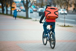 Courier on bicycle deliver an order from the fast food restaurant. Delivery boy on bicycle delivering food, takeaway. Man delivering food with red backpack, riding bicycle trough city street