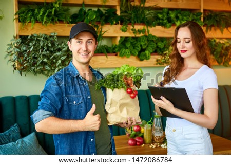 Courier service worker delivering fresh food to a happy woman client signing some documents on the kitchen at home. Online grocery shopping from the internet - shop