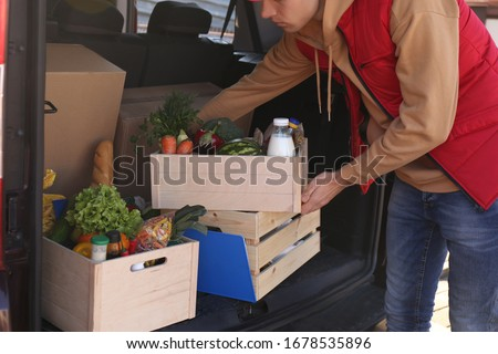 Courier taking crate with products from car, closeup. Food delivery service