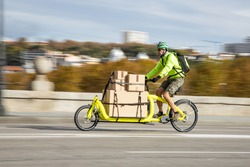 courier traveling with his cargo bike through the city, lateral view