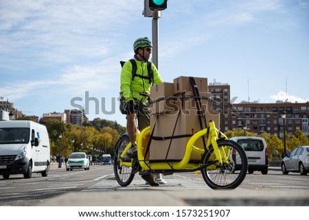 courier traveling with his cargo bike through the city, lateral view stock photo