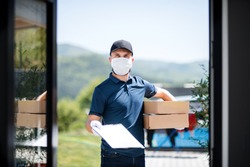 Courier with face mask delivering parcel, corona virus and quarantine concept.