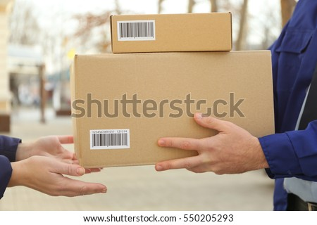Courier with parcel in doorway, closeup (it's not real QR code)