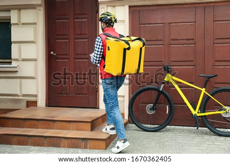 Courier with thermo bag and clipboard near customer's house. Food delivery service