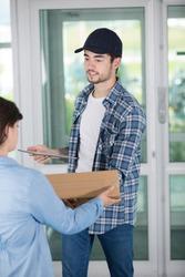 courrier delivering parcel holding digital tablet