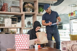 Courrier giving the goods to the girl wearing hijab in the coffe shop.