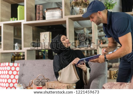 Courrier giving the goods to the girl wearing hijab in the coffe shop. Photo stock ©