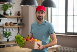 Courrier. Man in a red hat holding the box with groceries on the table