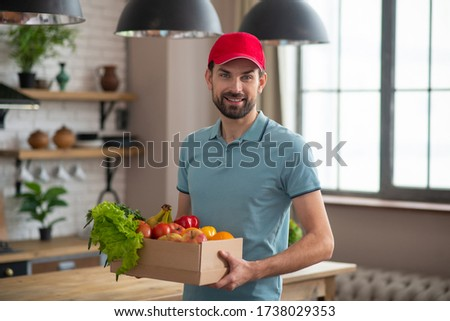 Courrier. Man in a red hat holding the box with groceries on the table Photo stock ©