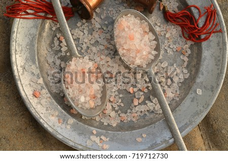 course pink Himalayan salt on pewter plate and pewter spoons and with red tasseled bells from the region #719712730