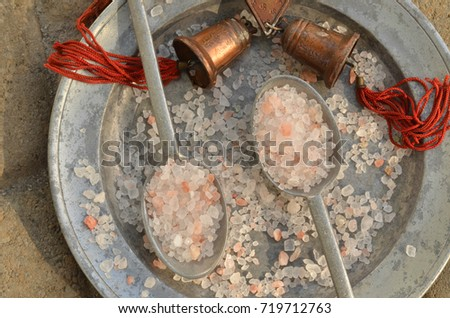 course pink Himalayan salt on pewter plate and pewter spoons and with red tasseled bells from the region #719712763