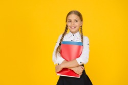 Courses for gifted children. Basic level. Happy schoolgirl hold textbooks yellow background. Little schoolgirl back to school. Small schoolgirl wear uniform. Cute schoolgirl. School education