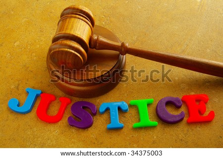 "court gavel with play letters spelling ""justice"""