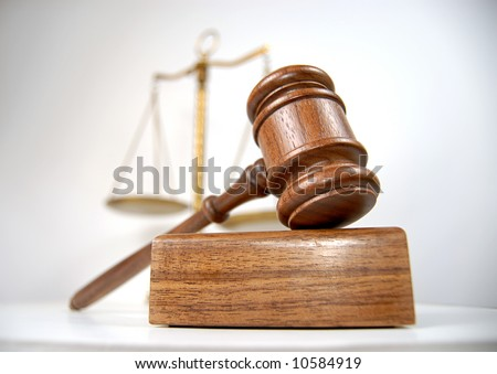 Courtroom detail with a gavel and scales of justice in the background