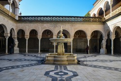 Courtyard in Seville, Moorish style of architecture. The courtyard is lit by the sun.