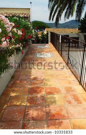 Courtyard of mediterranean villa in French Riviera with ceramic tile walkway