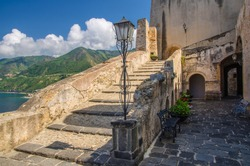 Courtyard old medieval knight's castle on rock Castello Ruffo with stone ancient walls, street lamp, vases with flowers and blue sky background, Scilla, Tyrrhenian sea, Calabria, Southern Italy