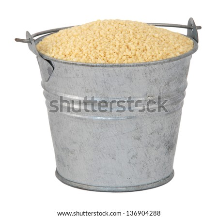 Cous cous in a miniature metal bucket, isolated on a white background