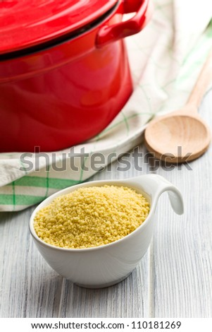 couscous in bowl on wooden table