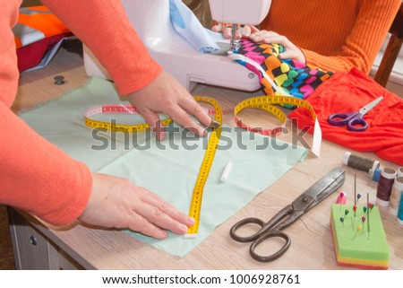 Couturier sews a dress in the studio. Fashion designer making a pattern on a red piece of tissue. Dressmaker work on the sewing machine #1006928761