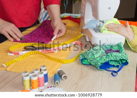 Couturier sews a dress in the studio. Fashion designer making a pattern on a red piece of tissue. Sewing machine is standing on the table beside them #1006928779