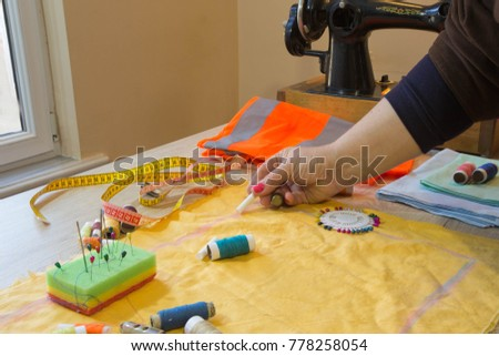 Couturier sews a dress in the studio. Fashion designer making a pattern on a red piece of tissue. Sewing machine is standing on the table beside them #778258054