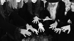 Coven of witches, modern witches gathered and do a ritual in the Park. Halloween, a group of different women like witches in black and hats.