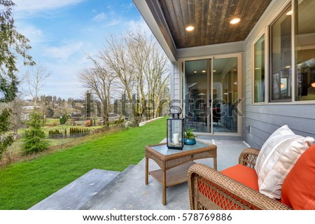 Covered back porch with concrete floor and stairs furnished with wicker chair topped with red cushions and wicker cocktail table overlooking peaceful neighborhood. Northwest, USA