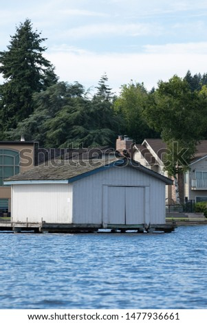 Covered boathouse at the end of a waterfront dock, in a maritime architecture scene #1477936661
