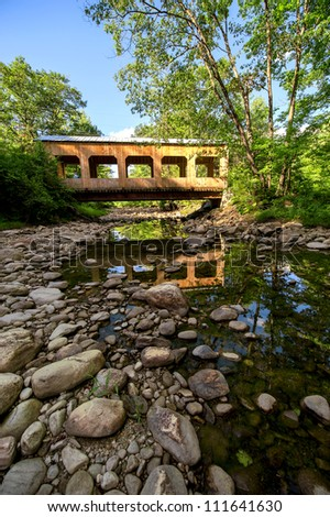 Covered bridge with reflection in vermont stream