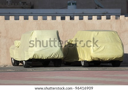 Covered cars parked by the wall. Ajman, United Arab Emirates